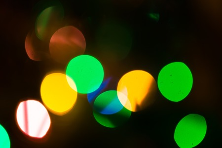 Christmas Bokeh background. Defocused colorful abstraction of lights on christmas tree photo