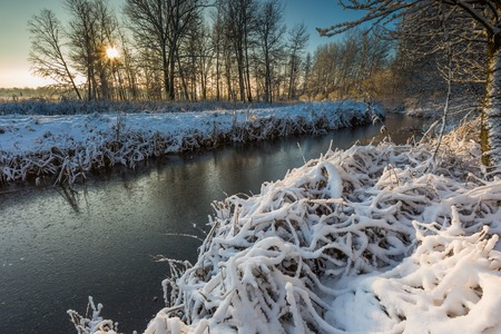Beautiful winter landscape with frozen river. Good sunny weather winter landscape. photo