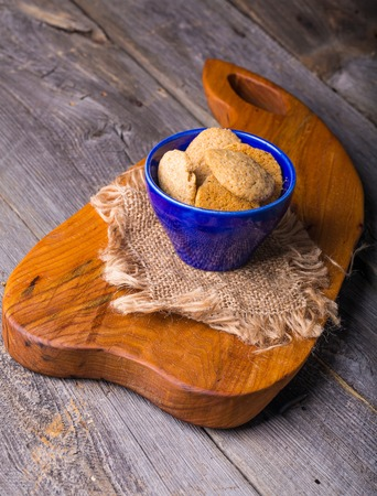 spelled: homemade spelled cookies in blue bowl on wooden table. Studio shot.