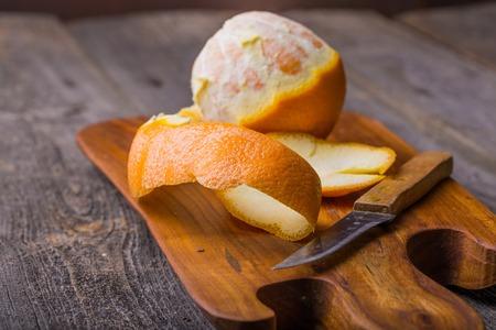 orange light: Peeled orange on wooden cutting board. Studio shot with mystic light effect Stock Photo