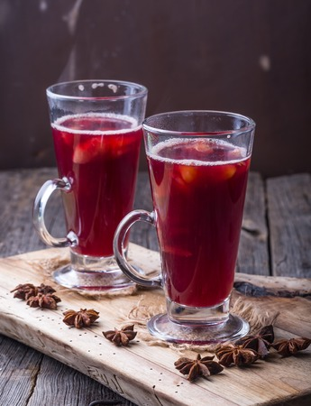 Mulled wine on wooden board and ancient table. Studio shot with mystic light effect photo