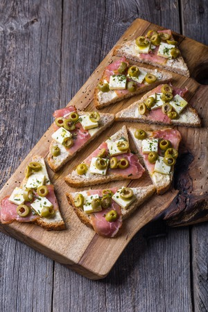 Small sandwiches with bacon, goat cheese and pitted olives on old cutting board photo