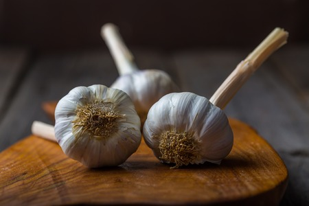 garlic bulbs on rustic wooden cutting board and wooden table. mystic light studio shot photo