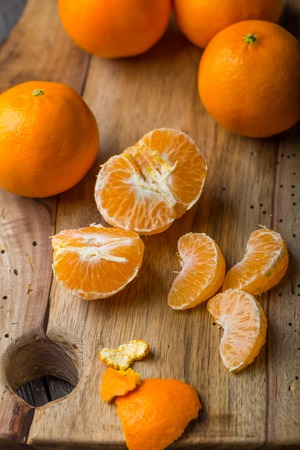 Fresh tangerines on wooden cutting board. Studio shot photo