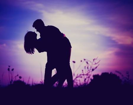 Silhouettes of hugging couple against the sunset sky. Photo with vintage mood Standard-Bild