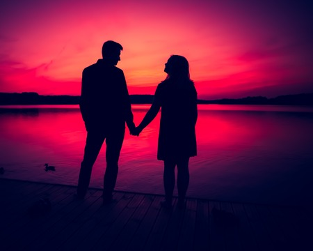 Silhouettes of hugging couple against the sunset sky. Photo with vintage mood.