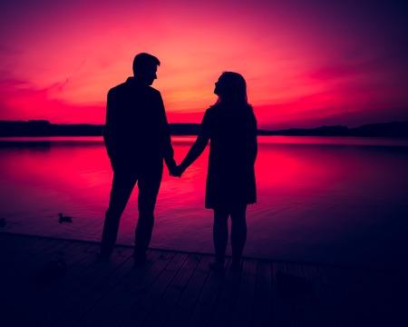 Silhouetten van knuffelen paar tegen de zonsondergang hemel. Foto met uitstekende stemming.