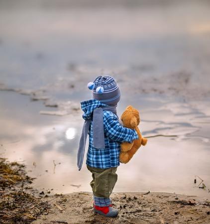 ni�o parado: Peque�o ni�o que se coloca en la orilla del lago con su oso de peluche. Paisaje hermoso Foto de archivo