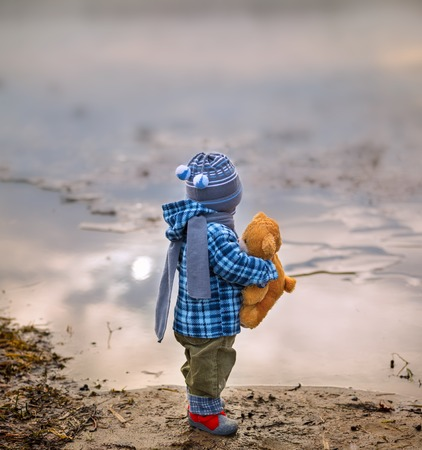 boy standing: Small child standing on lake shore with his teddy bear. Beautiful landscape