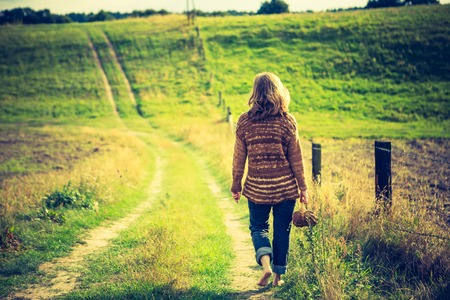 Girl in sweater walking by rural grassy road in countryside landscape. Photo with vintage mood photo