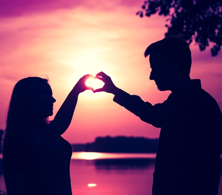 Couple doing heart shape with their hands on lake shore. People silhouettes vintage photo. photo