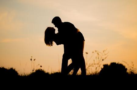 pareja bailando: Siluetas de abrazos pareja contra el cielo del atardecer. Foto con el estado de ánimo de la vendimia