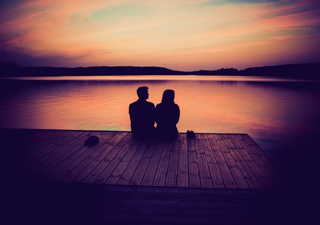 Silhouettes of hugging couple against the sunset sky. Vintage photo.