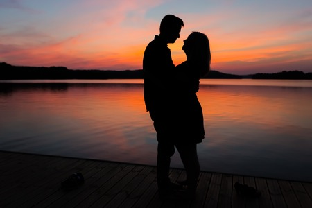 Silhouettes of hugging couple against the sunset sky. Photo with vintage mood. photo