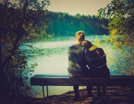 ハグのシルエットは、夕暮れ時の湖とベンチに座ってカップルします。ビンテージ写真。
