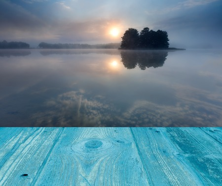 sunrise over lake. landscape with wooden planks floor on foreground photo