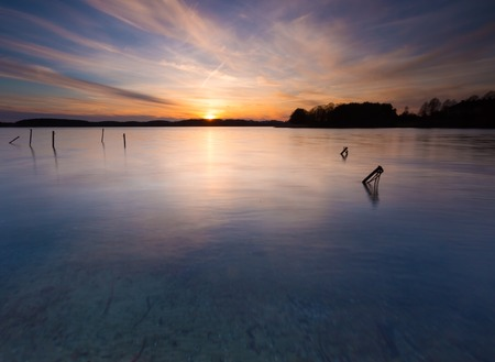long lake: Beautiful sunset over calm lake in Mazury lake district. After sunset sky reflecting in water, calm vibrant landscape. Krzywe lake near Olsztyn, Poland. Stock Photo