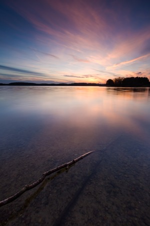 Beautiful sunset over calm lake in Mazury lake district. After sunset sky reflecting in water, calm vibrant landscape. Krzywe lake near Olsztyn, Poland. photo