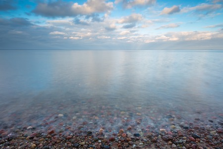 long: Beautiful long exposure landscape of rocky sea shore. Tranquil scene of Baltic sea near Gdynia in Poland. Stock Photo