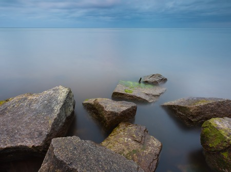 Beautiful Baltic sea landscape with stone breakwater. Tranquil long exposure landscape photo