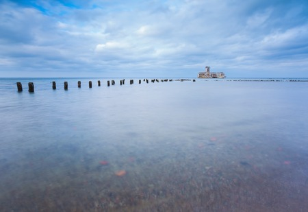 breakwaters: Beautiful view on Baltic rocky coast with old military buildings from world war II and wooden breakwaters.