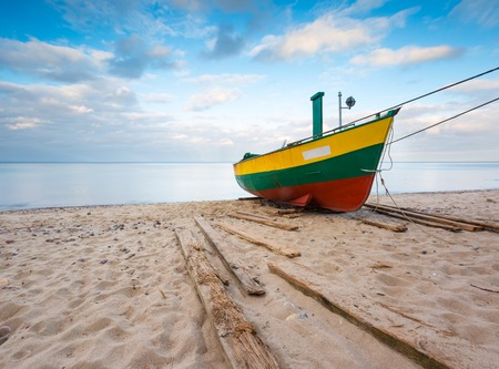 Fishing boat on Baltic sea shore. Beautiful long exposure seascape with fisherman boat. photo