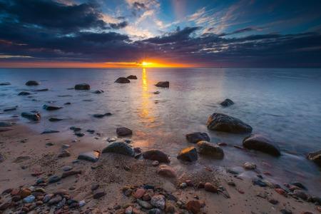 beautifu: Beautifu rocky sea shore at sunrise or sunset. Long exposure landscape. Baltic sea near Gdynia in Poland. Stock Photo