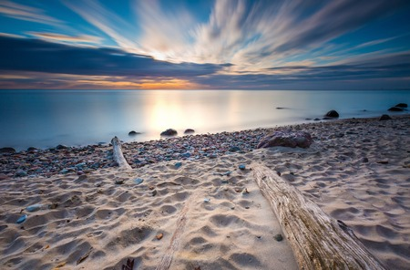 Beautifu rocky sea shore with driftwood trees trunks at sunrise or sunset. Baltic sea shore