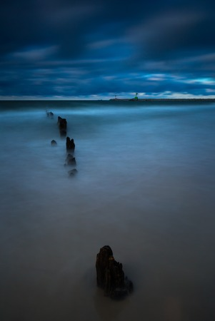 palisade: Baltic sea shore with old wooden breakwater palisade. Long exposure photo with dramatic sky Stock Photo