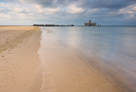 babie: Beautiful view on Baltic sandy coast with old military buildings from world war II and wooden breakwaters.