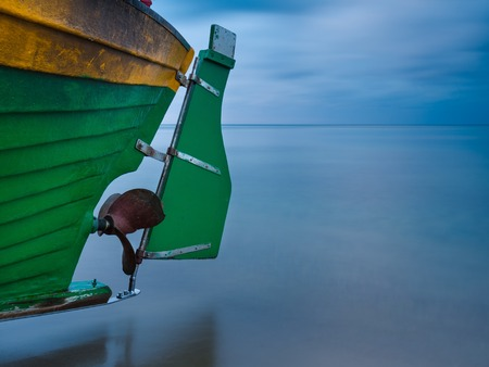 Landscape with Baltic Sea. Fishing boat part on the beach. Tranquil evening landscape. Long exposure photo photo