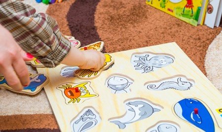puzzling: Little child puts the simple puzzle on the floor. Playing on floor. Stock Photo