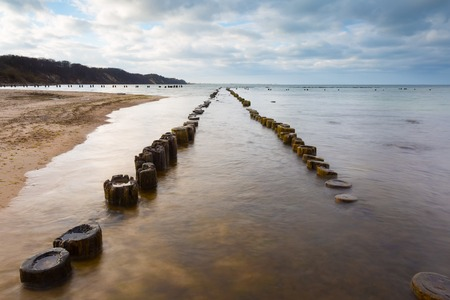 breakwaters: Beautiful view on Baltic sandy coast with old military buildings from world war II and wooden breakwaters. Long exposure photo