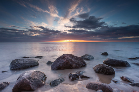 Beautiful rocky sea shore at sunrise or sunset. Long exposure landscape. Baltic sea near Gdynia in Poland. photo