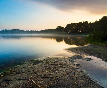 lake district: Beautiful sunrise over misty lake. Foggy morning over lake in Mazury lake district, Skand lake near Olsztyn in POland.