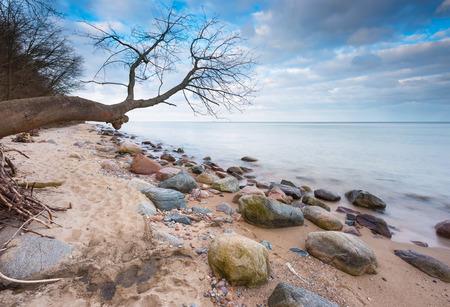 Beautiful long exposure landscape of rocky sea shore. Tranquil scene of Baltic sea near Gdynia in Poland. photo