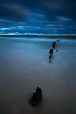 gorki: Baltic sea shore with old wooden breakwater palisade. Long exposure photo with dramatic sky Stock Photo