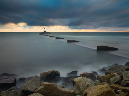 gorki: Mouth of the river Vistula in Gdansk. Long exposure seascape. Beautiful rocky breakwater on sea shore and protection walls on mouth of river.