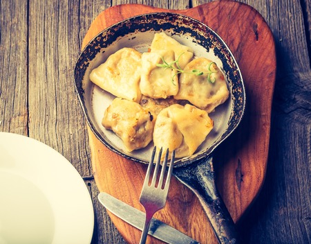 chinese food: Vintage photo of fried dumplings with onion  in a frying pan.