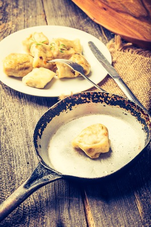 lomography: Vintage photo of fried dumplings with onion  in a frying pan.