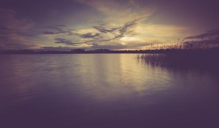 Vintage photo of beautiful sunset over calm lake. Landscape photogrpahed in Mazury lake district. photo