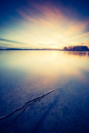 Vintage photo of beautiful sunset over calm lake. Landscape photogrpahed in Mazury lake district.