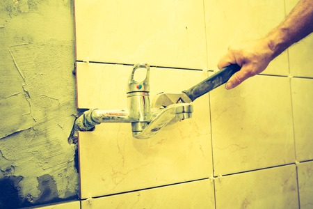 Vintage photo of plumbers hands tightening a water pipe. Authentic and accurate content depiction. photo
