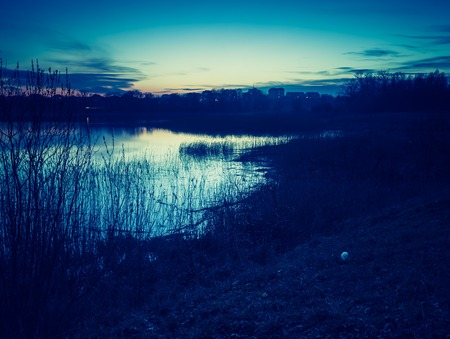 Vintage photo of beautiful sunset over calm lake in Mazury lake district. photo