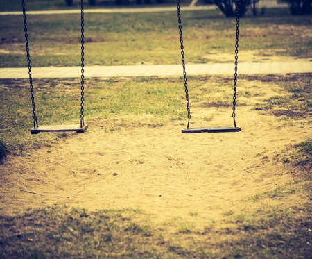 cross recess: Vintage photo of empty swing on children playground in city. Old fashioned colors photography.