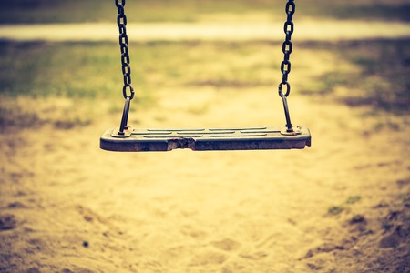 cross recess: Vintage photo of empty swing on children playground