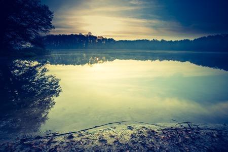 Vintage photo of sunset lake, calm landscape with old photo mood.
