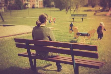 Uitstekende foto van moeder en kind op de speelplaats. Moeder zitten en kijken spelend kind.