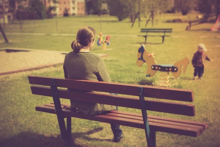 Vintage photo of mother and child on playground. Mother sitting and watching playing child.