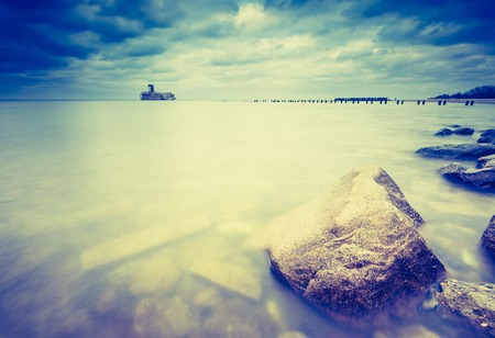 breakwaters: Vintage photo of beautiful view on Baltic sandy coast with old military buildings from world war II and wooden breakwaters. Long exposure photo Stock Photo